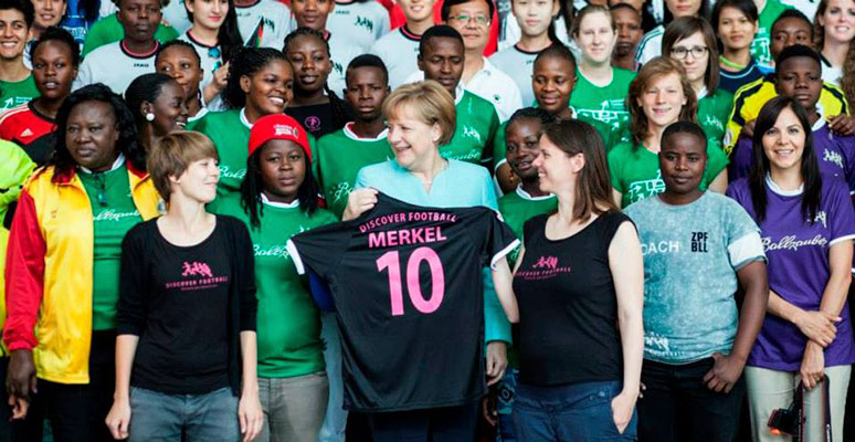 Merkel y Discover Football. Foto: Discover Football
